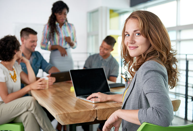 business woman at her laptop looking towards the camera, four other workers are in the background conversing