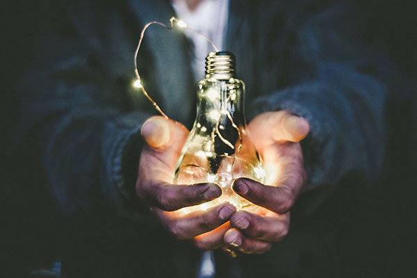man's hands holding lit lightbulb