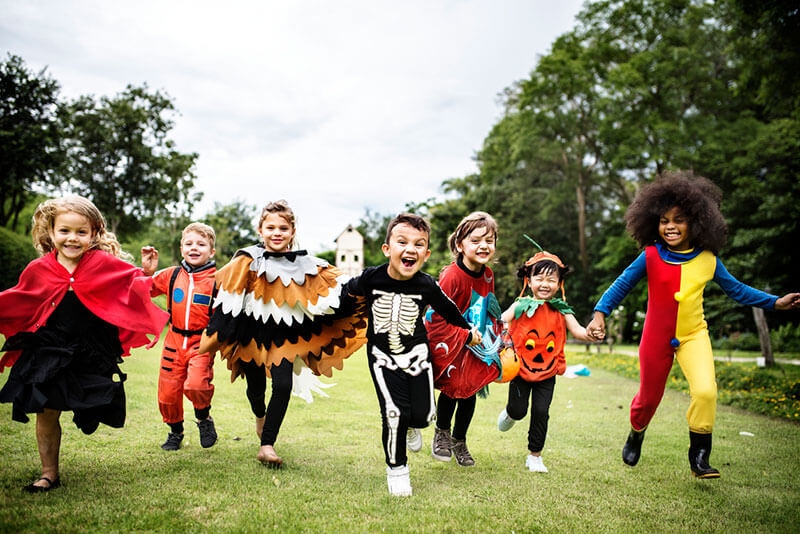 children dressed for halloween running towards the camera, looking happy